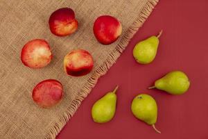Draufsicht von Pfirsich und Birnen auf einem roten Hintergrund