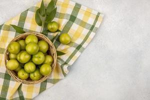 Draufsicht auf grüne Pflaumen im Korb foto
