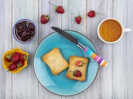 Draufsicht auf frische Erdbeeren und Marmelade auf geröstetem Brot