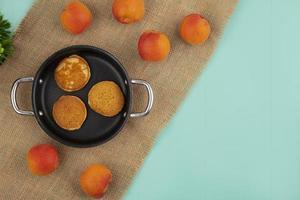 Draufsicht von Pfannkuchen in Pfanne und Aprikosen auf Sackleinen auf blauem Hintergrund mit Kopienraum foto