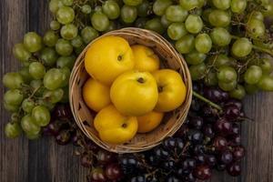 Draufsicht von Nektakoten und Trauben herum auf hölzernem Hintergrund