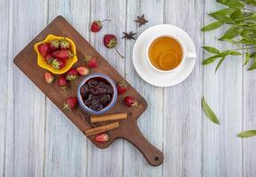 Draufsicht auf frische Erdbeeren und Marmelade mit Zimtstangen