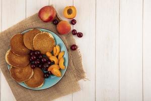 Draufsicht auf Pfannkuchen mit Kirschen und Aprikosenstücken