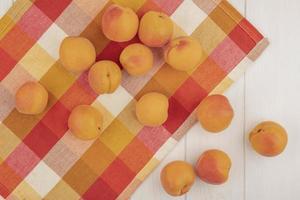 Draufsicht des Musters von Aprikosen auf kariertem Stoff und auf hölzernem Hintergrund
