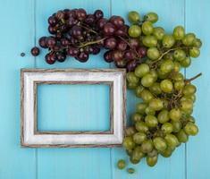 Draufsicht von Trauben und Rahmen auf blauem Hintergrund mit Kopienraum foto