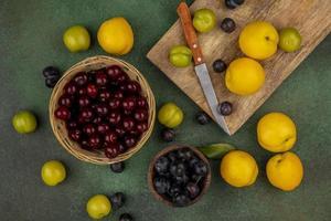 Draufsicht auf frische gelbe Pfirsiche mit grünen Kirschpflaumen und Kirschen