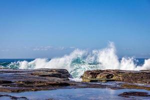 Wellen plätschern auf Felsen am Strand