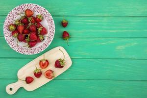 Draufsicht von frischen Erdbeeren auf einer Schüssel mit Erdbeerscheiben auf einem hölzernen Küchenbrett mit Kopierraum