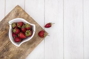 Draufsicht von frischen Erdbeeren auf einer weißen Schüssel auf einem hölzernen Küchenbrett auf einem weißen hölzernen Hintergrund mit Kopienraum