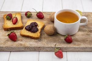 Draufsicht auf köstliche Erdbeeren mit Brot und Tee