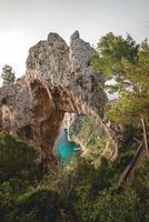 graue Felsformation über türkisfarbenem Meer