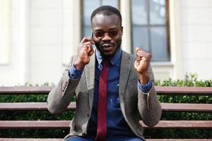 Afroamerikanermann spricht auf dem Smartphone, das draußen auf der Bank sitzt