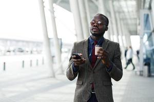 Afroamerikaner Geschäftsmann hört die Musik in seinem Smartphone foto