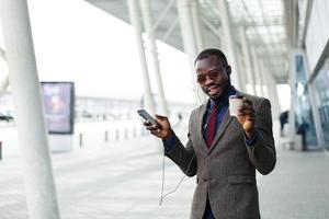 glücklicher afroamerikanischer Geschäftsmann tanzt, während er die Musik hört