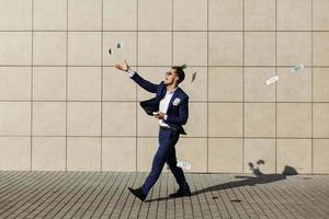 Ein junger Mann tanzt mit Geld auf der Straße