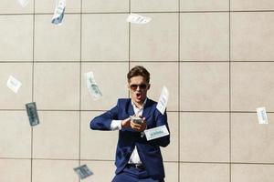 junger Geschäftsmann geht durch Dollars und tanzt auf der Straße