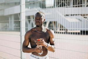 schöner Afroamerikanermann, der eine Flasche Wasser hält