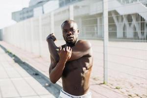 Der hübsche Afroamerikaner streckt sich vor einem Training im Freien