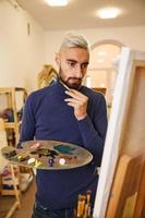 Der blonde Mann zeichnet ein Gemälde mit Öl