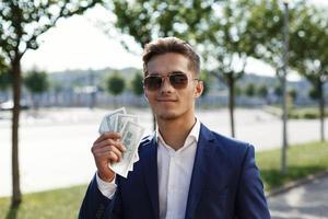 Der junge Geschäftsmann zeigt seinen Gewinn