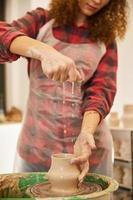 Frau streut Wasser auf eine Keramikware
