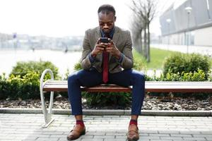 Afroamerikaner Geschäftsmann arbeitet in seinem Smartphone