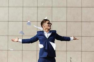 junger Geschäftsmann wirft zerrissene Papiere weg