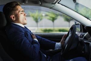 gutaussehender Geschäftsmann fühlt Schmerzen am Lenkrad im Auto sitzen