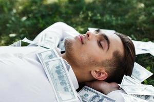 hübscher junger Mann in einem weißen Hemd liegt auf dem Boden bedeckt mit amerikanischen Dollars