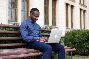 glücklicher Afroamerikanermann arbeitet an seinem Laptop, der draußen auf der Bank sitzt