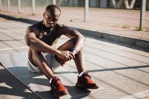 Afroamerikaner Mann sitzt müde auf dem Boden, nachdem er seine Übungen gemacht hat
