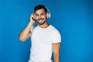 süßer Mann lächelt und hört etwas in den Kopfhörern foto