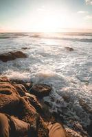 Person, die auf Felsen neben Strand sitzt