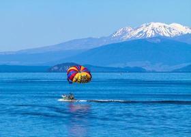 See Taupo, Neuseeland, 2020 - eine Parasailing-Gruppe, die auf einem Boot in der Nähe von Bergen reitet
