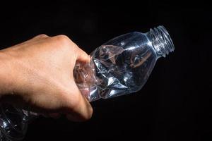 Hand hält eine Plastikflasche auf schwarzem Hintergrund