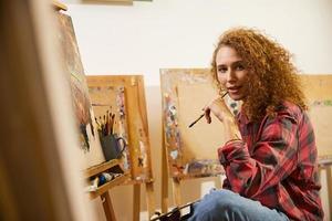Porträt der schönen rothaarigen lockigen Künstlerin mit Pinsel während ihrer Arbeit