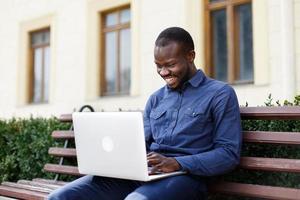 Mann lacht während der Arbeit am Computer foto