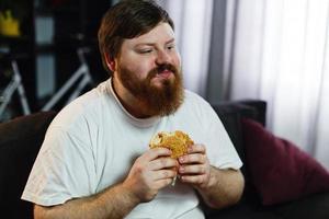 Mann isst einen Hamburger beim Fernsehen foto
