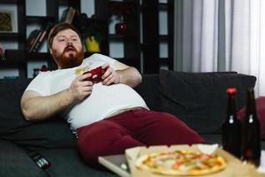 glücklicher dicker Mann im schmutzigen Hemd spielt Videospiele foto