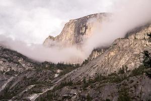 Berg von Wolken bedeckt und von Bäumen umgeben