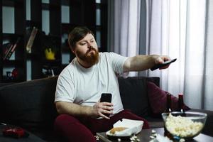 Mann schaltet die Kanäle im Fernsehen auf dem Sofa foto