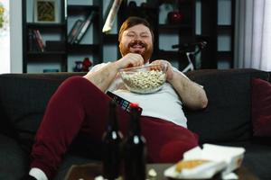 lachender dicker Mann sitzt auf dem Sofa, isst Popcorn und sieht fern foto