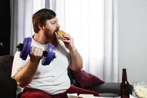 Mann, der einen Hamburger isst, während er Gewichte hebt foto