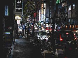 Osaka, Japan, 2018-Touristen gehen nachts durch die geschäftigen Straßen der Stadt