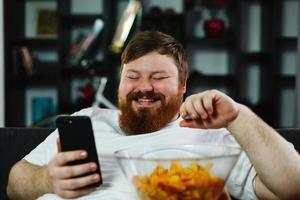 Mann mit einem Bier, das Chips isst und auf sein Telefon schaut foto
