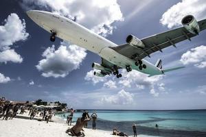 st. Martin, 2013-Touristen drängen sich am Strand von Maho, während sich niedrig fliegende Flugzeuge der Landebahn über der Küste nähern