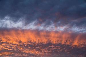 Streifen von goldenem Sonnenlicht über die Wolken