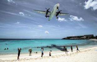 st. Martin, 2013-Touristen drängen sich am Strand von Maho, während sich niedrig fliegende Flugzeuge der Landebahn über der Küste nähern foto