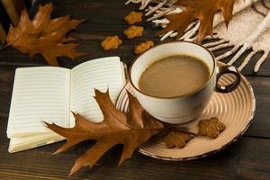 Tasse Kaffee mit Blättern, Notizbuch und Keksen