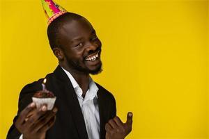 glücklicher niedlicher Geschäftsmann, der in die Kamera lächelt und eine Geburtstagstorte hält